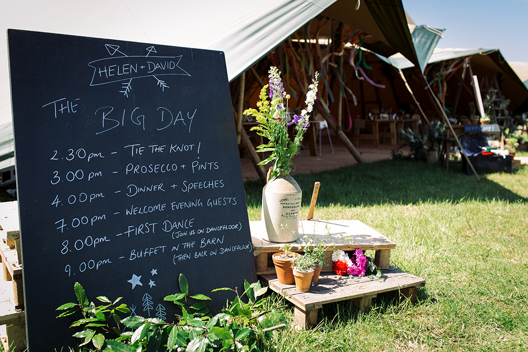 order of the day on a chalk board at a festival style wedding