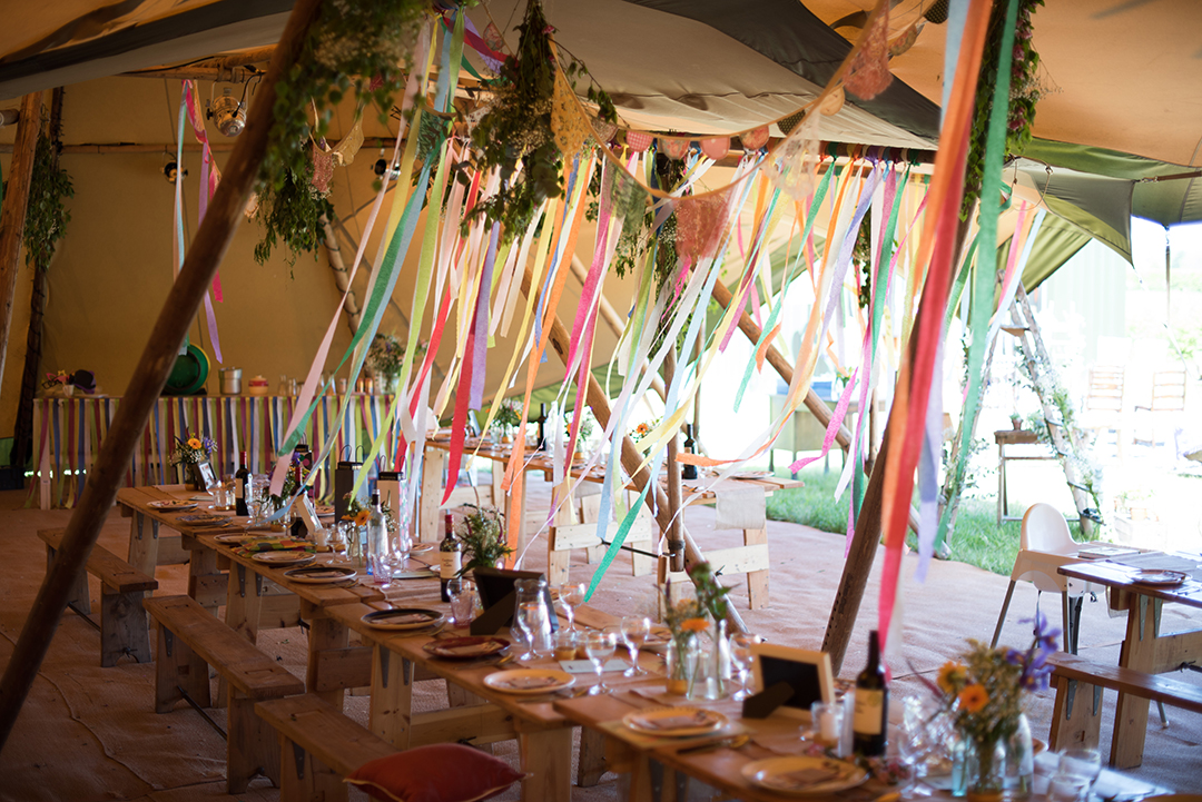 tipi with bright colourful streamers and decor for a festival wedding