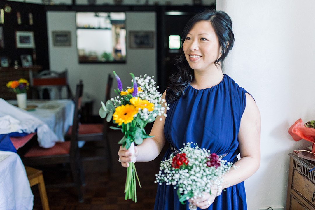 bridesmaid with colourful bouquet at a festival style wedding