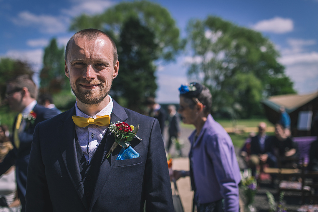 groom in blue suit and bow tie at a festival style wedding