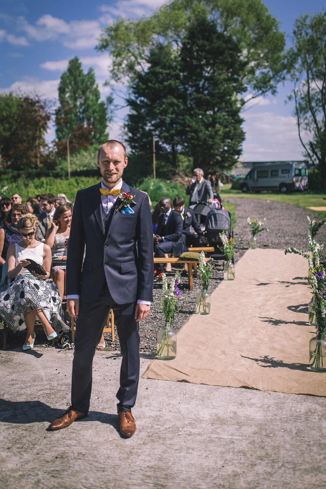 groom with blue suit and bow tie at a festival style wedding