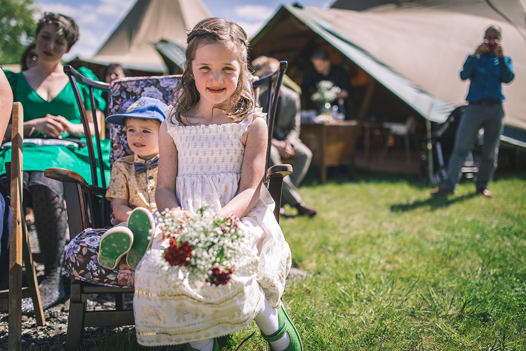 flower girl with wildflower bouquet at a festival style wedding