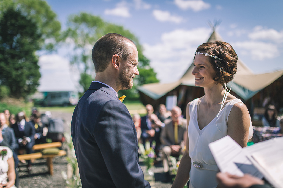 outdoor wedding ceremony with tipi in the background at a festival style wedding