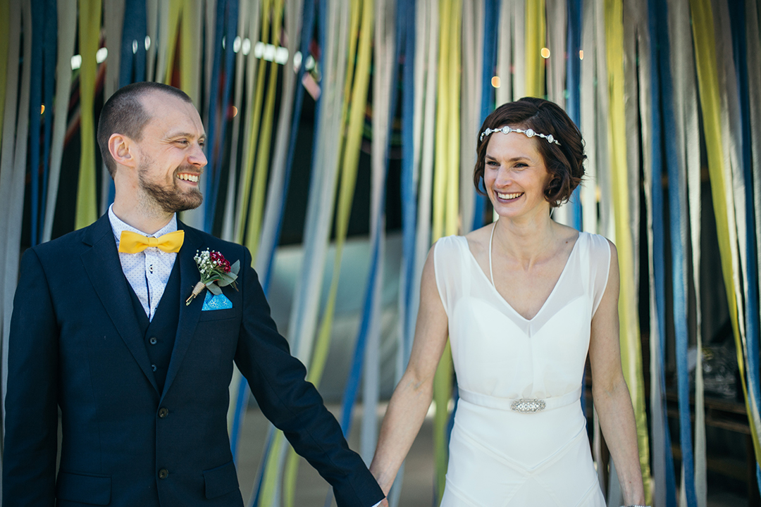 bride and groom in front of streamers at a festival style wedding