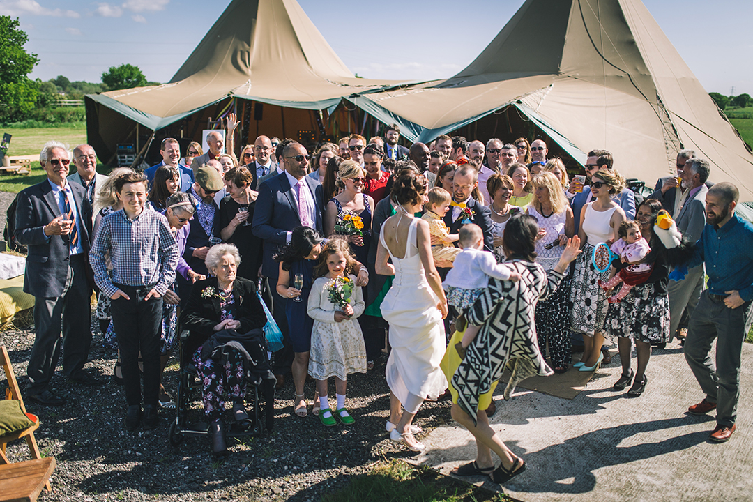 guests infront of a teepee at a festival style wedding