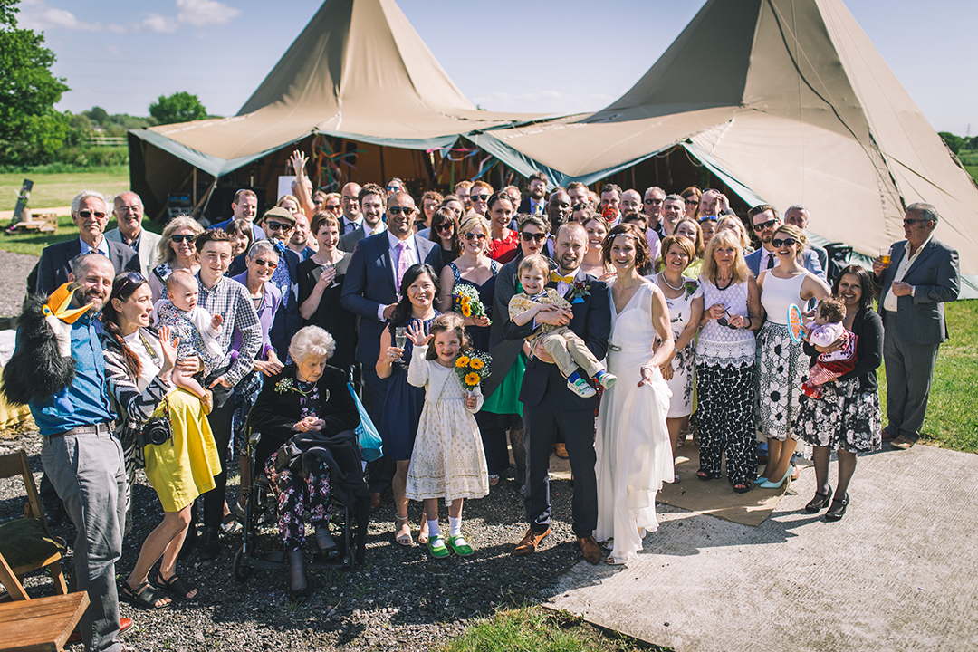 wedding party infront of a tipi and teepee at a festival style wedding