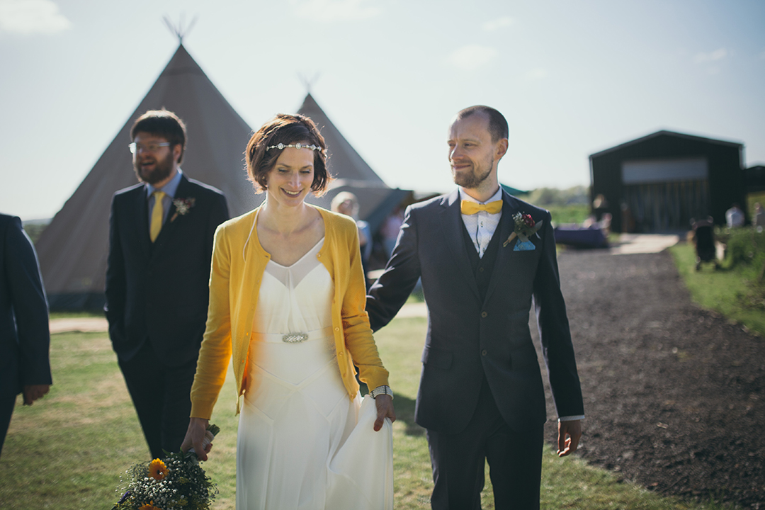 bride and groom with tipis at a festival style wedding