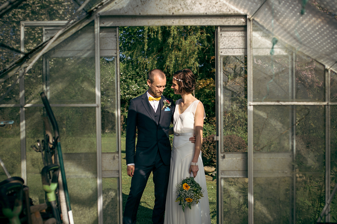 bride and groom in a green house at a festival style wedding
