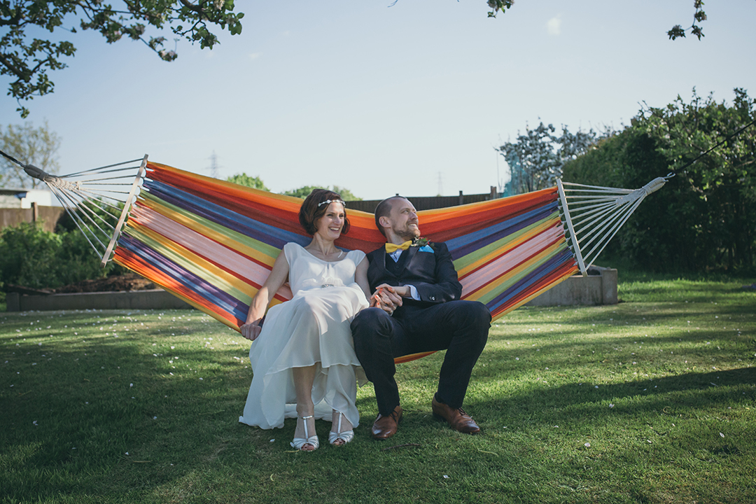 Bride and groom on hammock at a festival style wedding