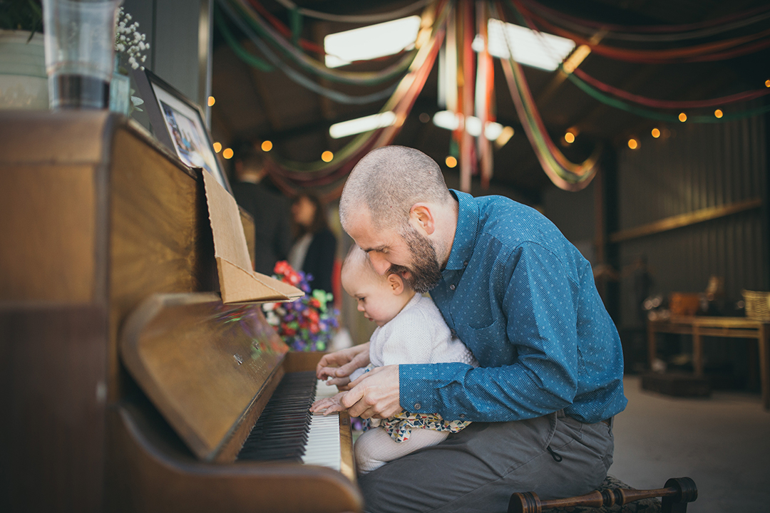 guests playing a piano at a festival style wedding