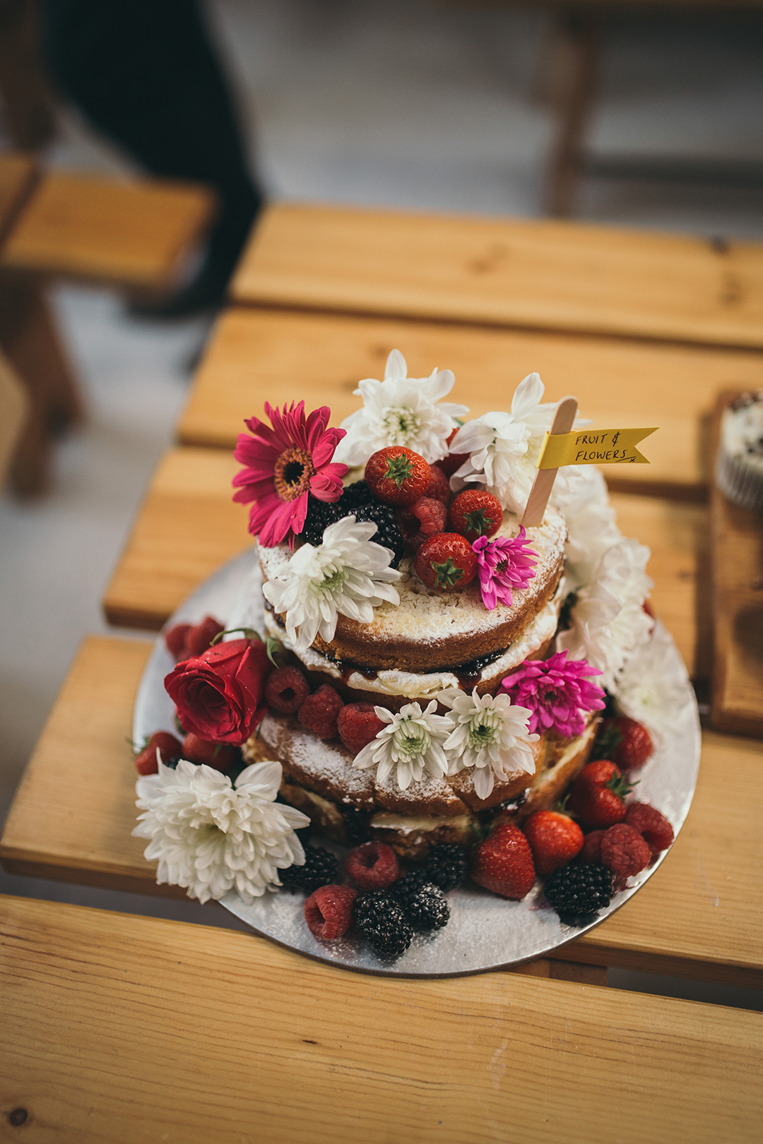 naked wedding cake with fruit and flowers at a festival style wedding