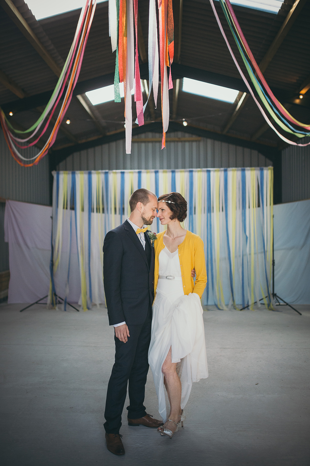 bride and groom with streamers at a festival style wedding