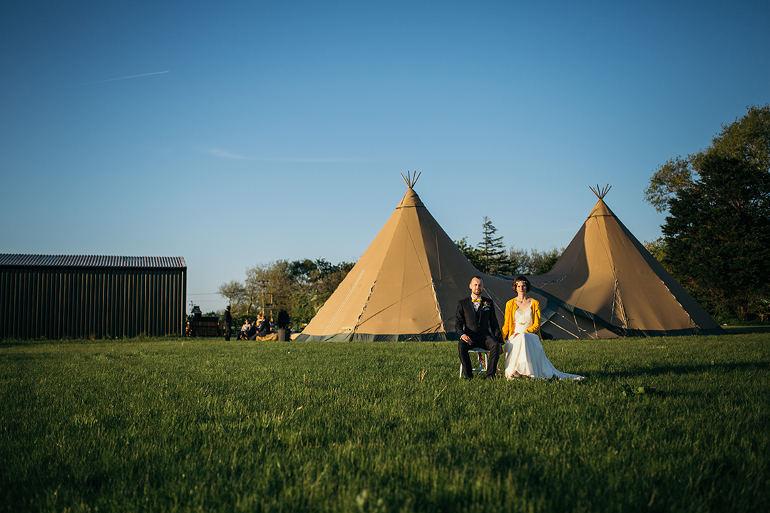 bride and groom in front of a wedding tipi at an outdoor wedding venue