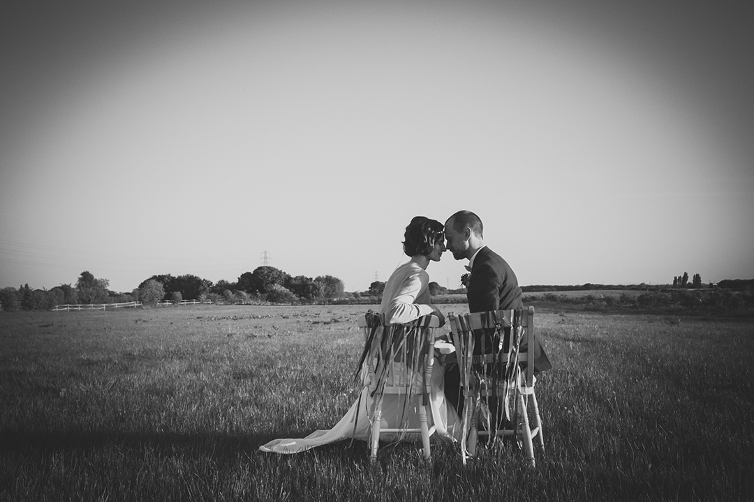 bride and groom on chairs at a festival style wedding