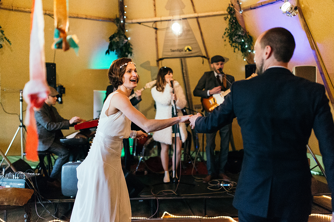 bride and groom first dance at a festival wedding with a tipi