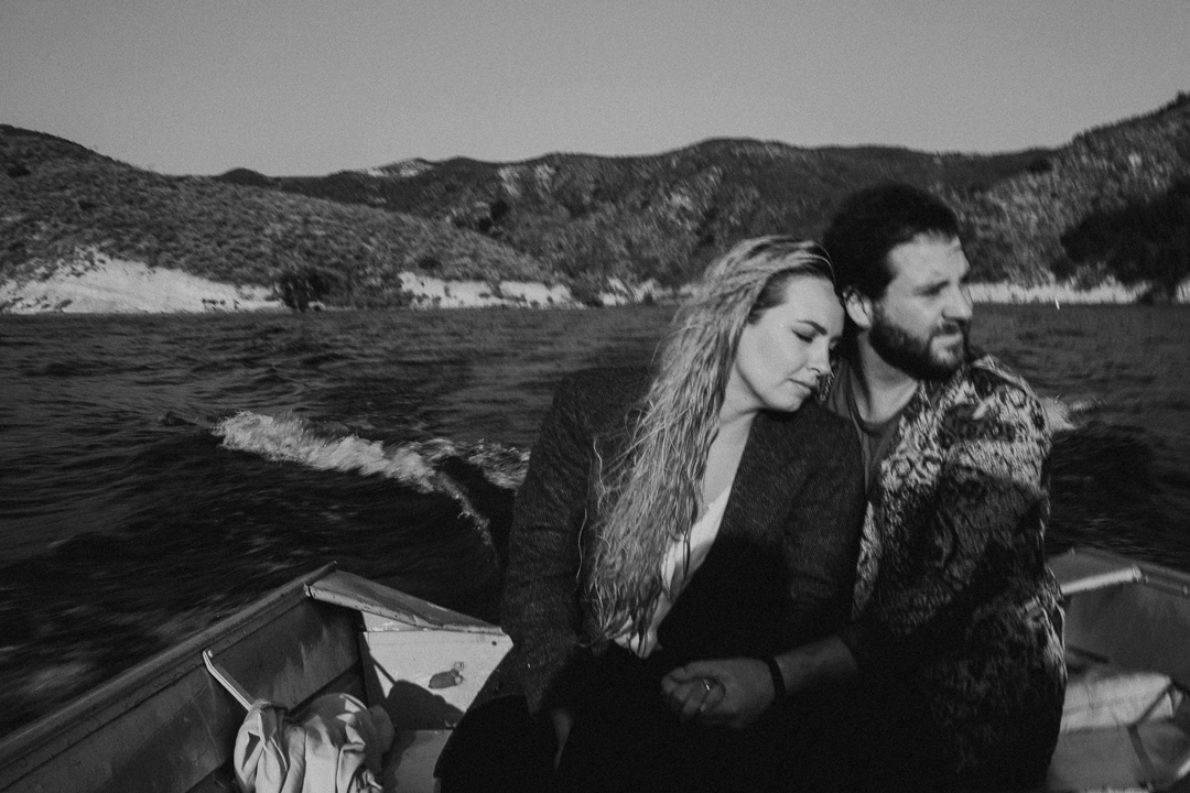couple embracing in boat at moody and artistic engagement shoot with couple in the water at beautiful couple shot captured at the waterside of Lake Casitas engagement shoot