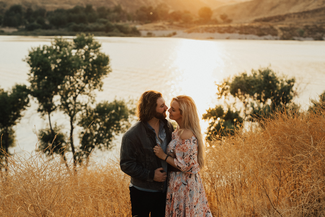 beautiful sunset couple shot by the waterside of couple embracing in boat at moody and artistic engagement shoot with couple in the water at beautiful couple shot captured at the waterside of Lake Casitas engagment shoot