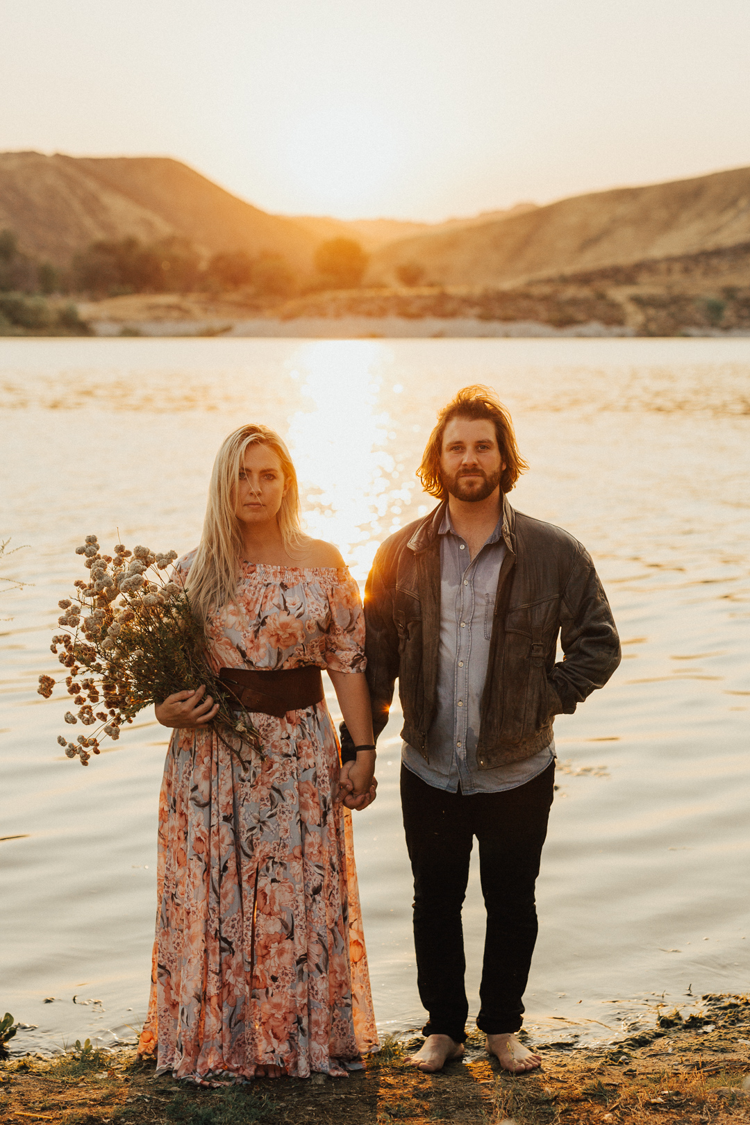 bohemian couple standing in the water with an over sized flower bouquet at couple embracing in boat at moody and artistic engagement shoot with couple in the water at beautiful couple shot captured at the waterside of Lake Casitas engagement shoot