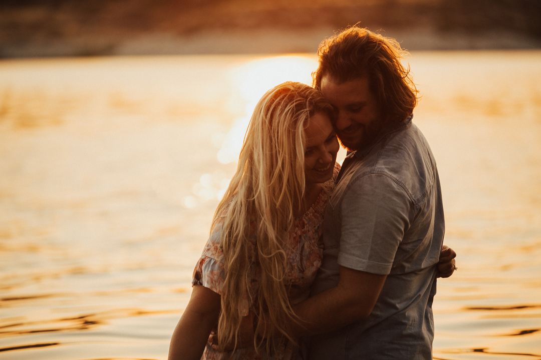 couple embracing in the water at sunset at Lake Casitas engagement shoot