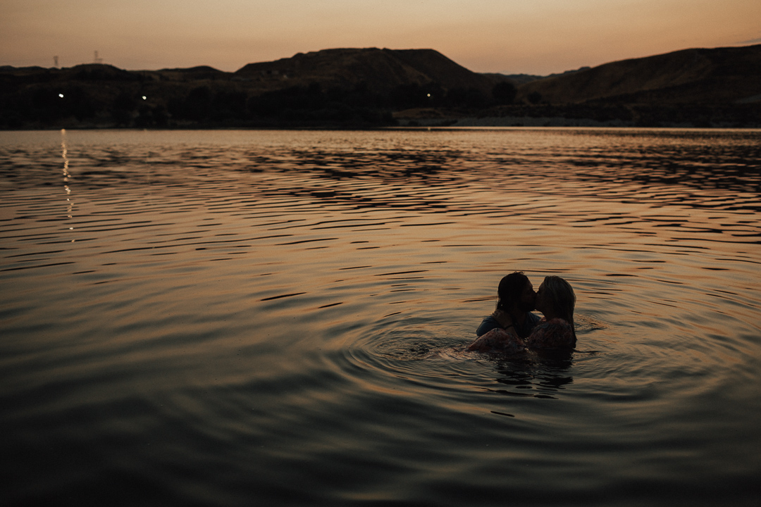 couple kissing in the water at sunset at Lake Casitas engagement shoot