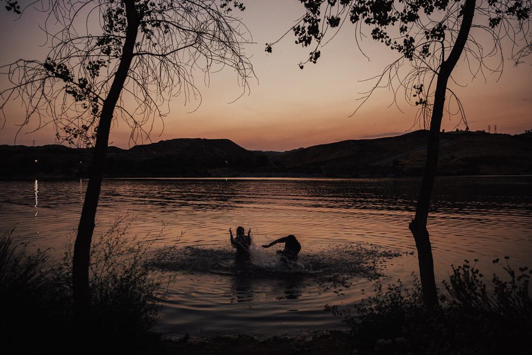couple splashing and having fun in the water at sunset at Lake Casitas engagement shoot
