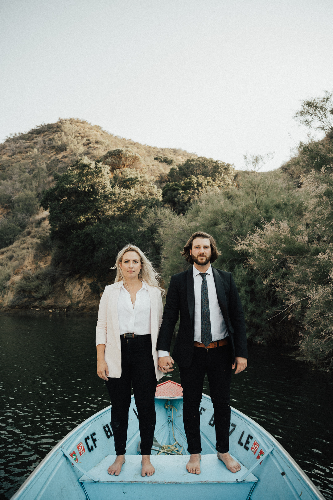 couple holding hands in boat at their engagement shoot at beautiful couple shot captured at the waterside of Lake Casitas