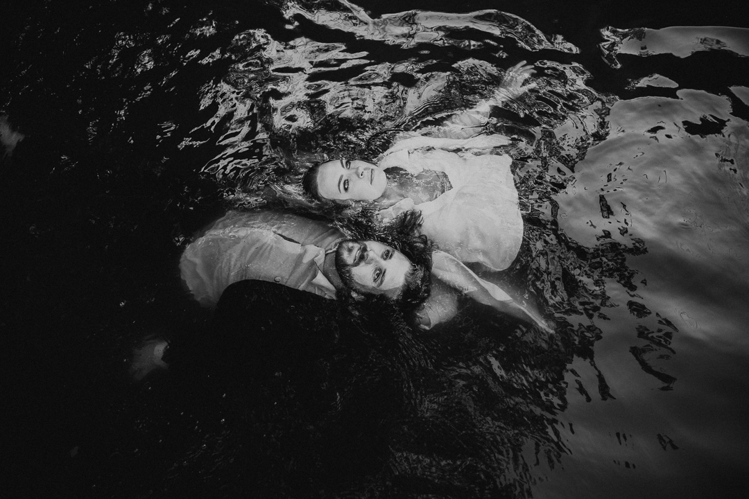 moody and artistic engagement shoot with couple in the water at beautiful couple shot captured at the waterside of Lake Casitas