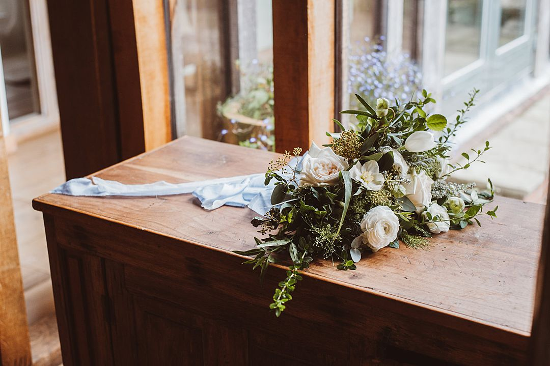 Oversized wedding bouquet with white flowers and green foliage tied with a blue ribbon