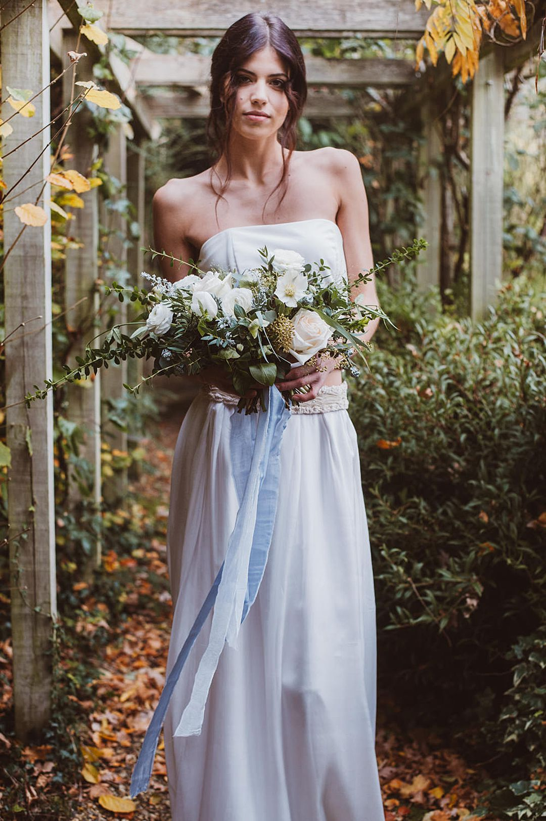 Bride with white, green and blue wedding bouquet | Paradise bodice made from silk crepe worn with an embellished silk knit and bead belt and bridal skirt by Jessica Turner Designs