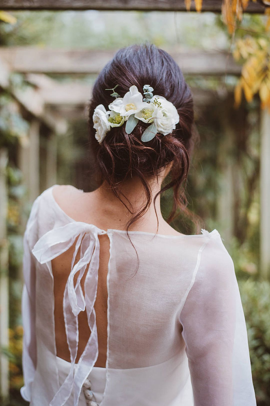 Boho style wedding hair up do with white flowers. Bride wearing bridal bodice with a silk separate top with bird embroidery by Jessica Turner Designs