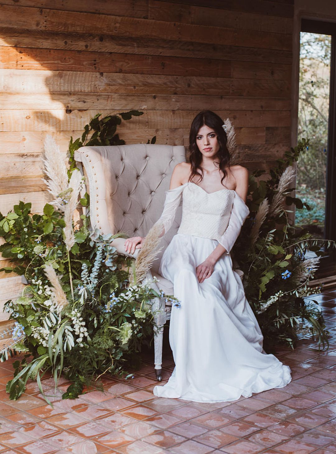 boho bride in wedding chair surrounded by white, green and blue wild flowers wearing Jessica Turner Bridal Separates